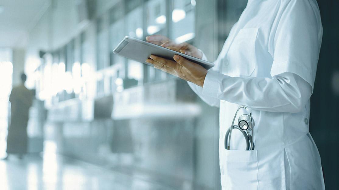 Eine Person aus dem medizinischen Bereich hält ein Tablet in den Händen.