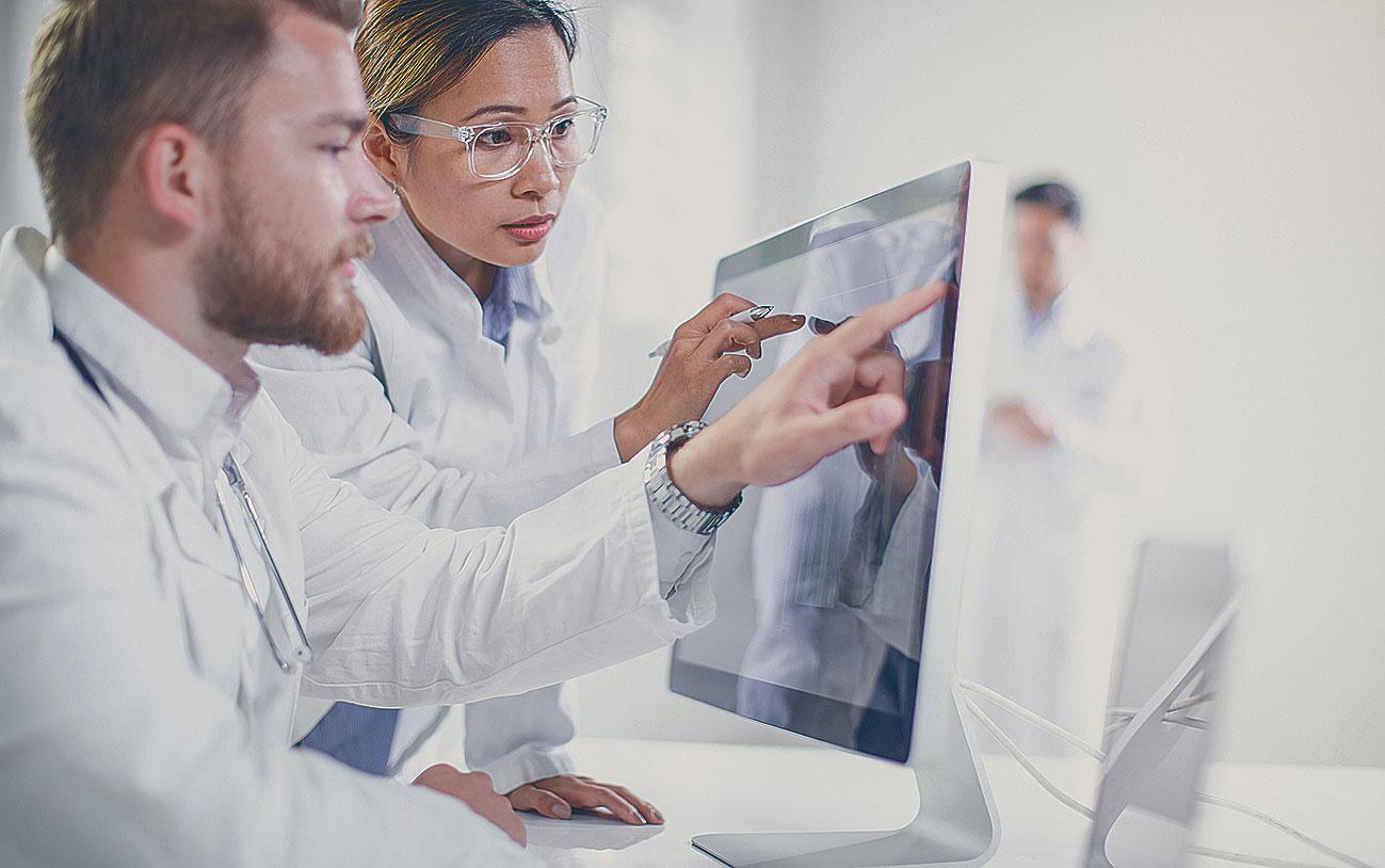 Darstellung von zwei Ärzte, die auf einen Bildschirm sehen.