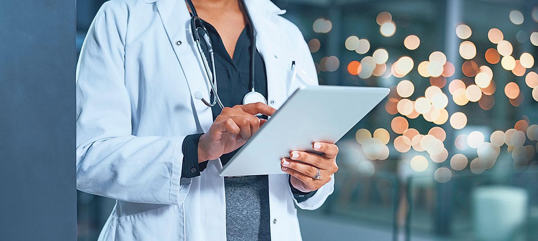 Medizinisches Personal mit einem Tablet in der Hand.