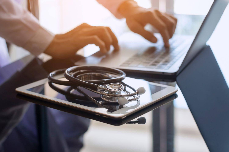 Abbildung, wo man ein Stetoskop sowie einen aufgeklappten Laptop erkennen kann.